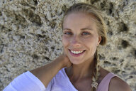 Portrait of smiling blond woman with rocky background - ECPF00310