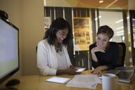 Smiling businesswomen reviewing paperwork in conference room - HEROF13552