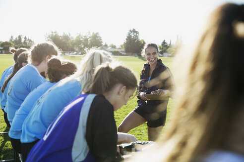 Smiling coach preparing middle school girl soccer team on field - HEROF13555