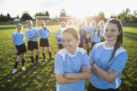 Smiling middle school girl soccer players looking away on sunny field - HEROF13558