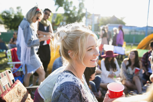 Smiling young woman drinking and hanging out at summer music festival campsite - HEROF13576