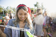 Smiling young woman blowing bubbles at summer music festival - HEROF13579