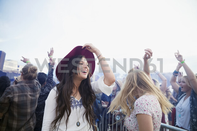 Smiling young women dancing in crowd at summer music festival - HEROF13582