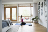 Pregnant woman practicing yoga on bedroom floor - HEROF13600