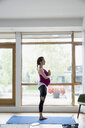 Pregnant woman practicing yoga tree pose at window - HEROF13603