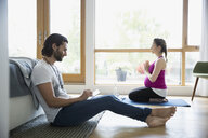 Pregnant couple practicing yoga and relaxing with digital tablet in bedroom - HEROF13609