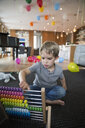 Serious boy playing with abacus in living room - HEROF13618