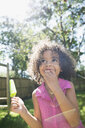 Smiling girl eating flavored ice and looking up in sunny backyard - HEROF13627