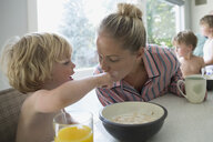 Son feeding cereal to mother at breakfast in kitchen - HEROF13633