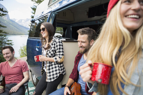Smiling friends hanging out drinking coffee outside camper van at lakeside - HEROF13636