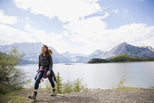 Smiling woman hiking at remote mountain lakeside - HEROF13639