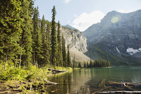 Scenic view of remote craggy mountain and sunny lake - HEROF13645