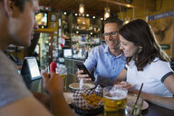 Smiling friends using cell phone in bar - HEROF13660