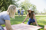 Smiling women friends laying blanket for picnic in grass in summer park - HEROF13666