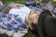 Serene man napping in grass in park - HEROF13669