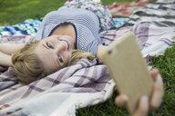 Smiling blonde woman taking selfie with camera phone on blanket in park - HEROF13672