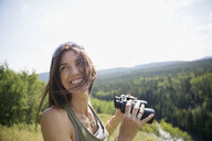 Smiling brunette woman with binoculars - HEROF13675