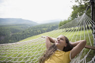 Serene girl laying in rural hammock looking up with hands behind head - HEROF13678