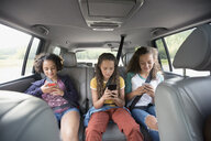 Sisters using cell phones in back seat of SUV - HEROF13681