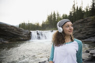 Teenage girl listening to music with headphones near remote waterfall - HEROF13684