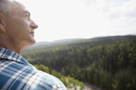 Serene mature man looking at remote treetop view - HEROF13690