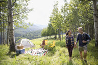 Senior couple holding hands outside sunny rural campsite - HEROF13693