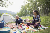 Senior couple enjoying picnic on blanket at rural campsite - HEROF13696