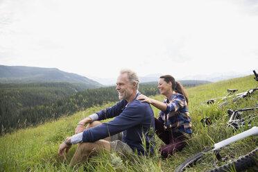 Senior couple relaxing near mountain bikes in remote rural field - HEROF13705