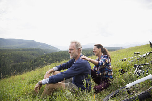 Senior couple relaxing near mountain bikes in remote rural field - HEROF13705