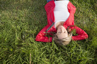 Serene woman laying relaxing with hands behind head in grass - HEROF13708