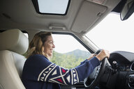 Smiling woman driving SUV - HEROF13720
