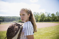 Portrait serious middle school girl softball player with baseball glove in outfield - HEROF13735