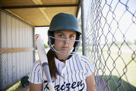 Portrait serious middle school girl softball player wearing batting helmet and holding bat in dugout - HEROF13738