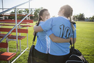 Portrait smiling middle school girl soccer teammates hugging and walking off field - HEROF13741