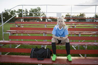 Portrait serious middle school girl soccer player listening to music with headphones and mp3 player on bleachers - HEROF13744