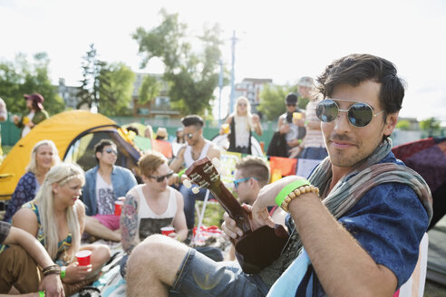 Portrait young man playing ukulele at summer music festival campsite - HEROF13750