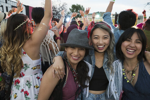 Portrait smiling young women in crowd at summer music festival - HEROF13753