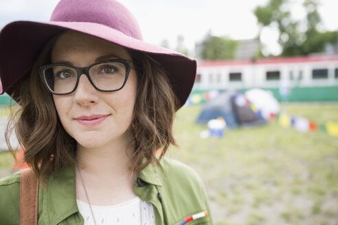 Portrait smiling young  brunette woman wearing floppy hat and eyeglasses at summer music festival campsite - HEROF13762