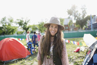 Portrait smiling young brunette woman wearing hat at summer music festival campsite - HEROF13765