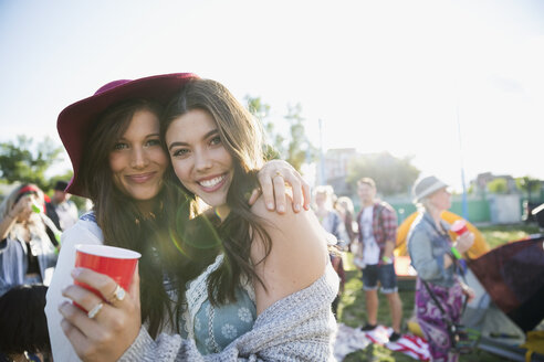Portrait smiling young women drinking and hanging out at summer music festival campsite - HEROF13771