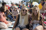 Portrait smiling young women at summer music festival campsite - HEROF13780