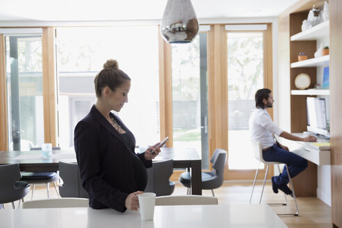 Pregnant businesswoman drinking coffee and texting with cell phone in morning kitchen - HEROF13783