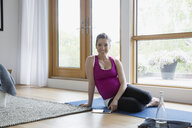 Portrait smiling pregnant woman with digital tablet practicing yoga on floor - HEROF13786