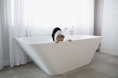 Portrait shy boy in killer whale costume hiding in bathtub - HEROF13792