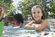 Portrait smiling girl drawing and painting at patio table - HEROF13795