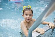 Portrait smiling boy at swimming pool ladder - HEROF13801