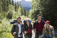 Portrait smiling couples hiking with backpacks and hiking poles on sunny trail in woods - HEROF13837