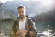 Portrait smiling bearded man hiking at sunny mountain lake - HEROF13843