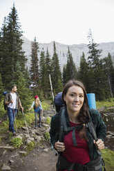 Portrait smiling woman hiking with friends on trail in remote woods - HEROF13846