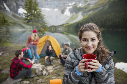 Portrait smiling woman drinking coffee at remote lakeside campsite - HEROF13849